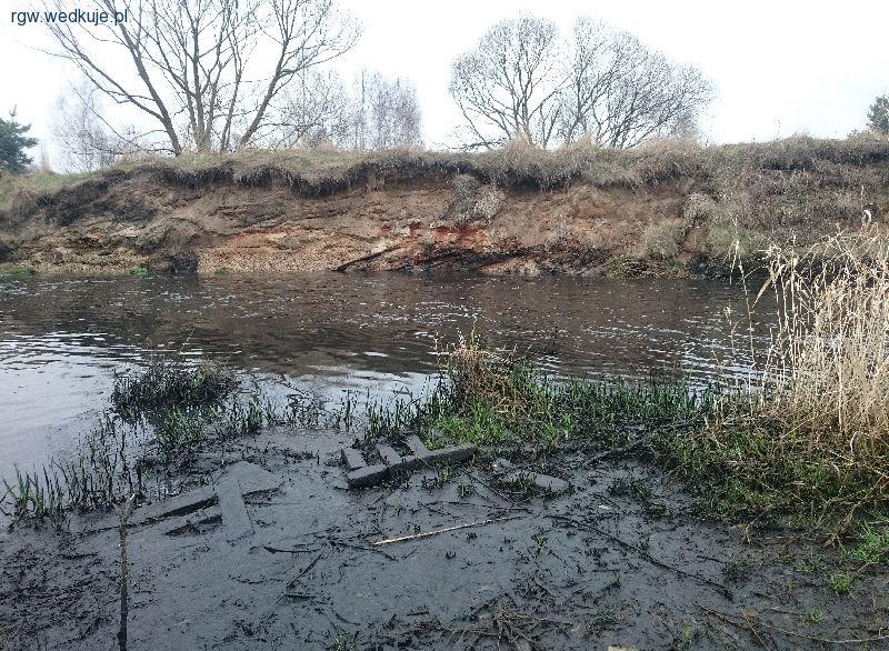 Niski stan wody widoczny po mule pod nogami i linii wody na przeciwnym brzegu.